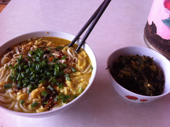 These noodles hit the spot. On the right is a dish of 酸菜or sour vegetables, a Yunnan favorite.