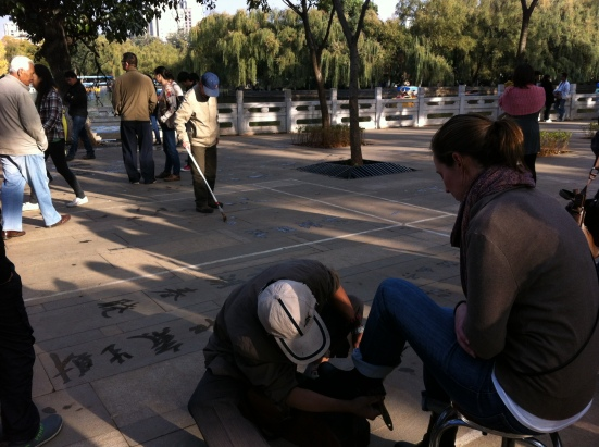 Water calligraphy in the park while I get my shoes shined